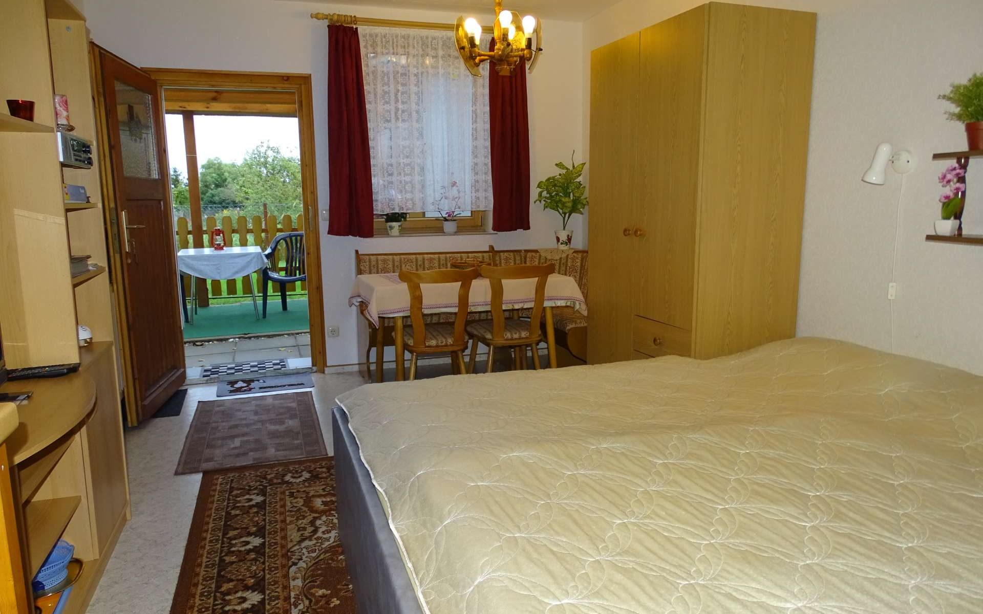 FeWo 2: Zimmer mit Bett, Sitzecke und Platz im Freien